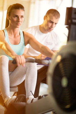 supervisi�n: Gym woman with supervision of a personal trainer doing exercise at the gym Foto de archivo