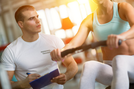 athletics: Young male trainer giving instructions to a woman in a gym