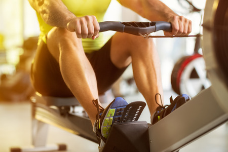 indoors: Fit man training on row machine in gym