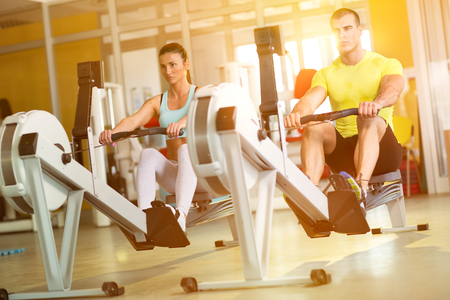 machine: Fit  couple on row machine in gym, sport, fitness, lifestyle, and people concept