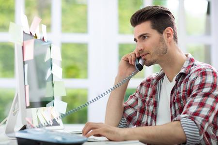 hablando por telefono: Hombre ocupado trabajando en la computadora