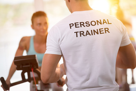 exercise equipment: Personal trainer on weights lifting training with  client Stock Photo
