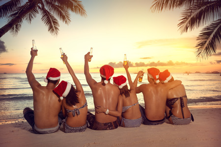 Christmas holiday on tropical vacation, group of friends in Santa hats sitting on beach