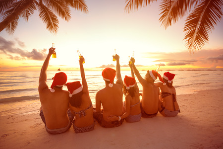 Back view of group people with raised hands holding a bottle of beer on beach, Christmas holiday Standard-Bild