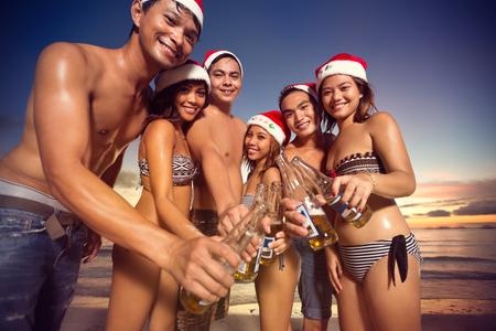 tomando agua: grupo de amigos felices con sombreros de Santa tostado