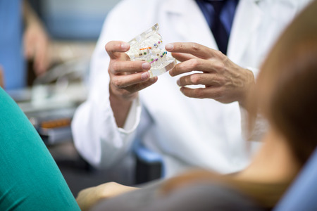Close up of dentist holding model of teeth with colorful braces Stock Photo