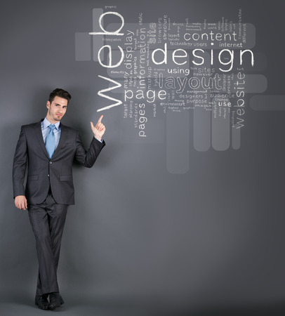 cloud network: Businessman standing in front of a wall with web design terms and pointing on it
