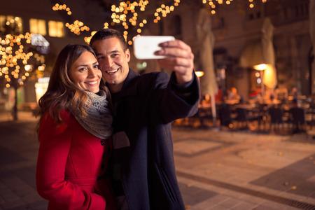 momentos felices juntos. Feliz joven selfie toma de pareja amorosa y sonriendo mientras está de pie fondo de Navidad