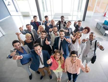 Portrait of thumb up smiling business people