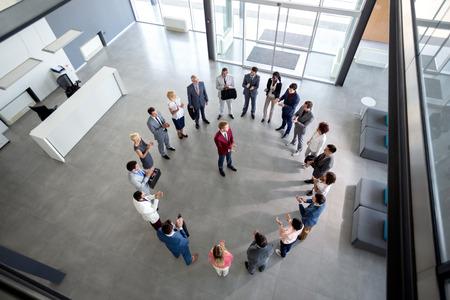 Vue de dessus de l'équipe satisfaite battements de mains avec le gestionnaire dans le centre du cercle