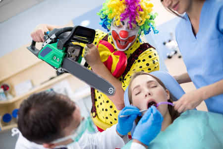 threatens: Crazy clown from horror threatens girl with chainsaw in dental clinic