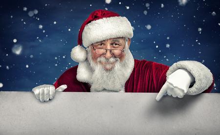Papá Noel que señala en la muestra en blanco blanco con sonrisa, en la nieve de fondo de invierno Foto de archivo