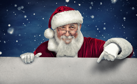 Santa Claus pointing in white blank sign with smile, on winter snow  background