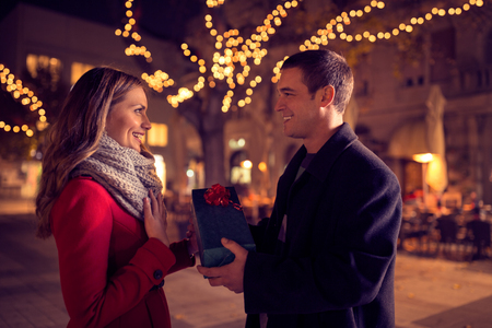romantic couples: Christmas gift, happy couple with Christmas and New Year gift on street