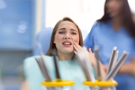 mouth pain: Nice young girl with toothache in dental chair hold sore spot
