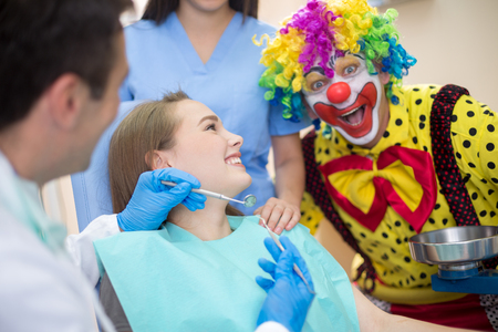 fanny: Colorful fanny clown in dental clinic draws attention to young girl