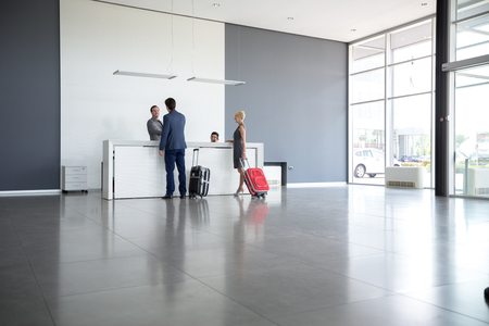 Passengers departing from business trip at hotel reception