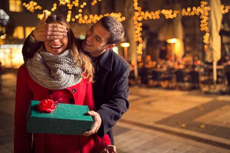 jovenes enamorados: El hombre guarda su novia ojos cubiertos mientras ella da un regalo, sorpresa rom�ntica para la Navidad Foto de archivo