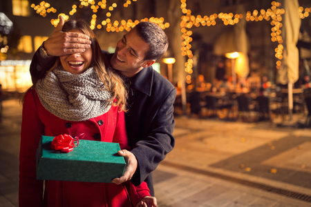 happy couple: Man  keeps his girlfriend eyes covered while  she giving a gift , romantic surprise for Christmas
