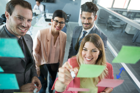 30 40 years: Creative business team looking at sticky notes on window