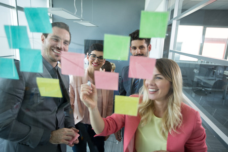 lluvia de ideas: Sonriendo parejas modernas que buscan en las notas adhesivas