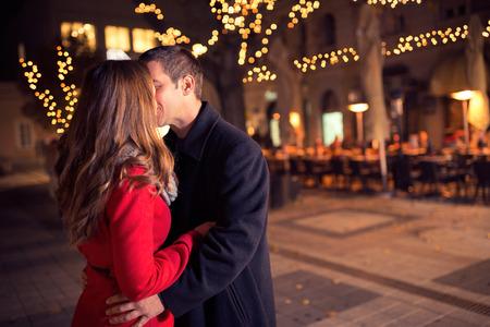 pareja besandose: joven pareja de enamorados besándose en el centro de la ciudad, Año Nuevo y Navidad.