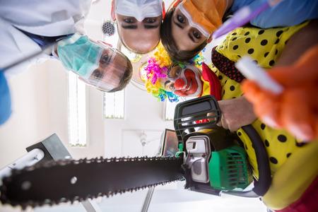 payaso: Delirio asustadizo con el equipo dental y el payaso loco con la motosierra en vista desde abajo
