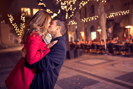 baiser amoureux: Jeune couple enlacé embrassant tendrement sur la rue de Noël