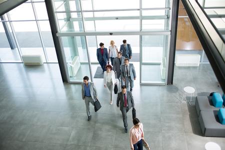 Grupa profesjonalnych ludzi biznesu chodzenie na drodze w budynku