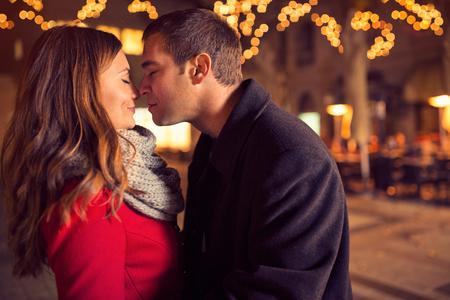 anochecer: Joven pareja cariñosa besándose tiernamente en la calle de la Navidad