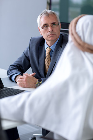 agal: Manager of company listen Arabian guest about their serious situation Stock Photo
