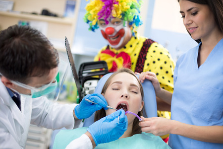 scary clown: Girl on unusual dental treatment with scary clown in background Stock Photo