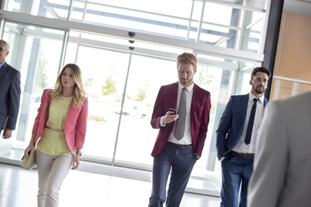 arrive: Group of young businessmen enter in airport foyer Stock Photo