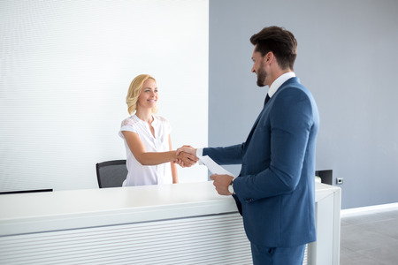reception table: Kind female receptionist wish welcome to guest Stock Photo