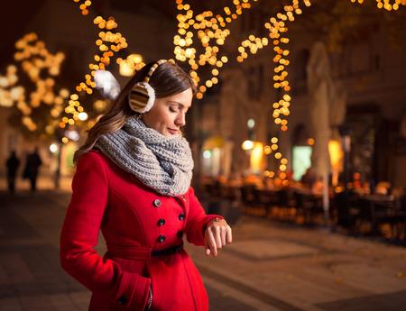 novio: mujer mirando su reloj en la calle mientras espera a su novio que llega tarde a una cita Foto de archivo