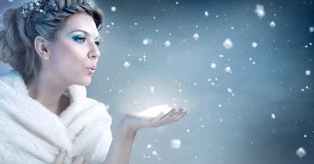 resfriado: Mujer del invierno que sopla nieve sobre fondo azul - reina de la nieve