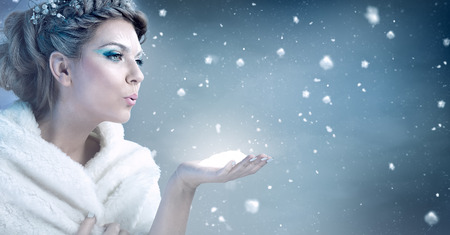 ice queen: Winter woman  blowing snow over blue background - snow queen