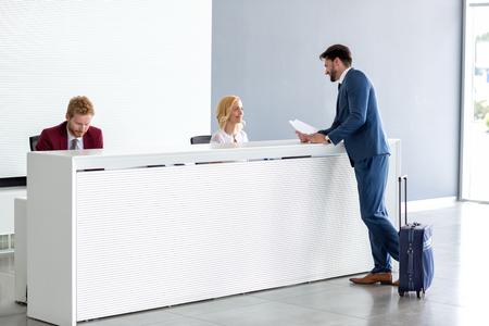 Junger stattlicher Geschäftsmann mit Rezeptionistin flirten