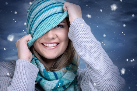 girl in a hat: smiling girl playing with her hat on winter background