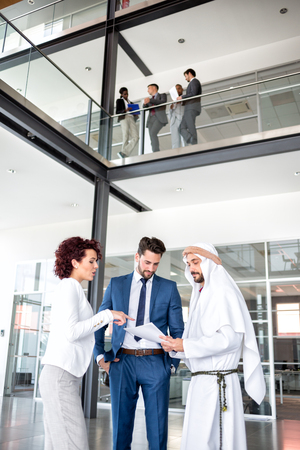 unsatisfied: Unsatisfied young managers on meeting with Arabian businessman, full length Stock Photo
