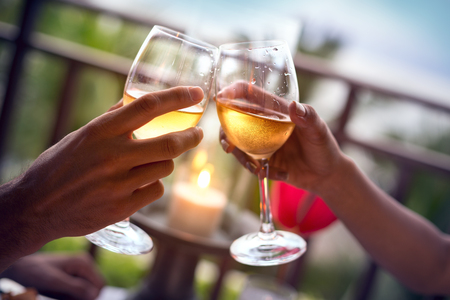 Hände des Mannes und der Frau mit einem Glas Weißwein jubeln