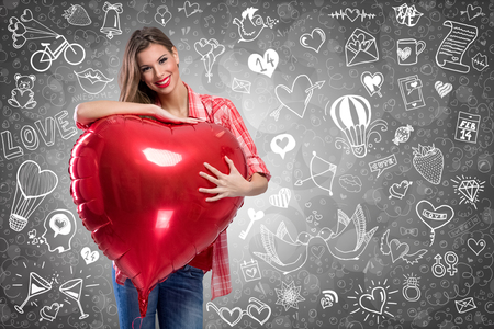 anniversary sexy: Smiling young woman holding a heart shaped balloon