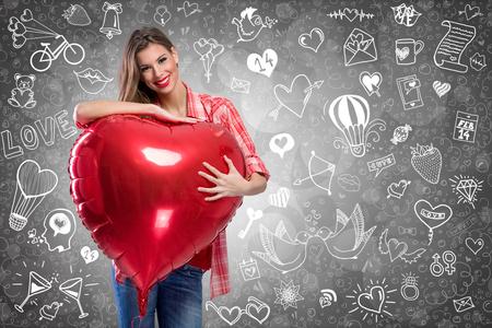 femme romantique: Sourire jeune femme tenant un ballon en forme de coeur