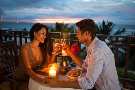 diner romantique: jeune couple appréciant un dîner romantique aux chandelles, en plein air