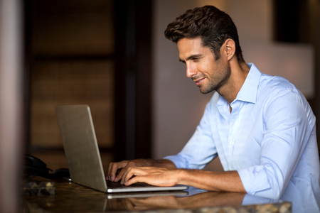 blogger: Portrait of a nice smiling man working at home on some project, he is sitting at a table looking at his laptop in front of him
