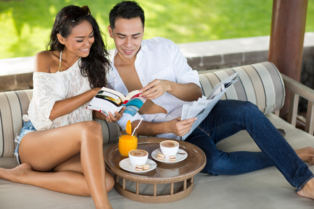 Smiling couple reading book together  while having drink on deck chair