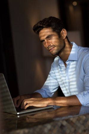 Goodlooking young man working on laptop computer