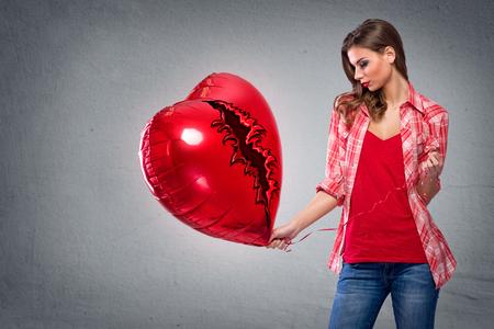 anniversary sexy: Beautiful woman looking at big heart shaped balloon