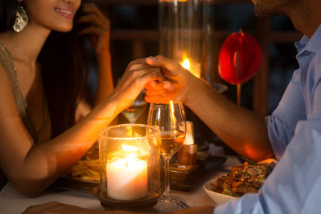 asia nude: Romantic couple holding hands together over candlelight during romantic dinner Stock Photo