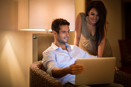 ambiance: Cheerful couple searching together data on laptop at home